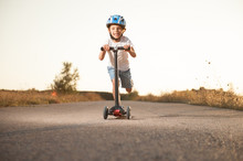 Healthy Little Boy In Helmet Riding Scooter On Road With High Speed Outdoor