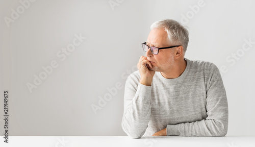 Obraz old age, problem and people concept - close up of senior man in glasses thinking - fototapety do salonu
