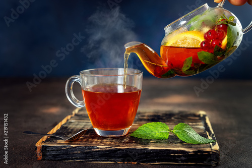 Pouring herbal hot tea in glass cup