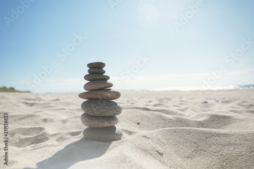 Pyramid of sea stones on the sand by the sea