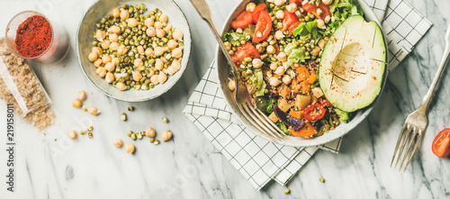 Vegan lunch bowl. Flat-lay of dinner with avocado, mixed grains, beans, sprouts, greens and vegetables over marble background, top view, horizontal composition. Vegetarian, diet food concept