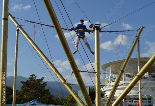 The boy gladly jumps on the bungee in the amusement Park against the blue sky