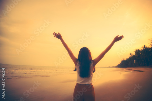 Fotobehang Draw Silhouette Asian woman raise up hand freedom and enjoy view of beautiful sunset sky on tropical beach in twilight time at Phuket province, Southern of Thailand