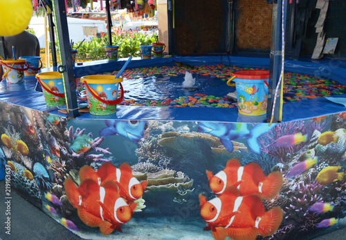 Foto  Fishing toy fish entertainment on a children's attraction in the Park