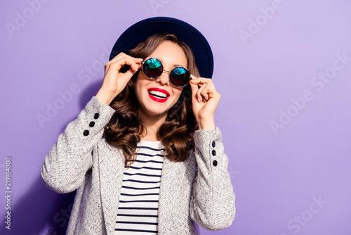 Valokuva  Portrait of funny carefree girl holding eyelets of glasses with