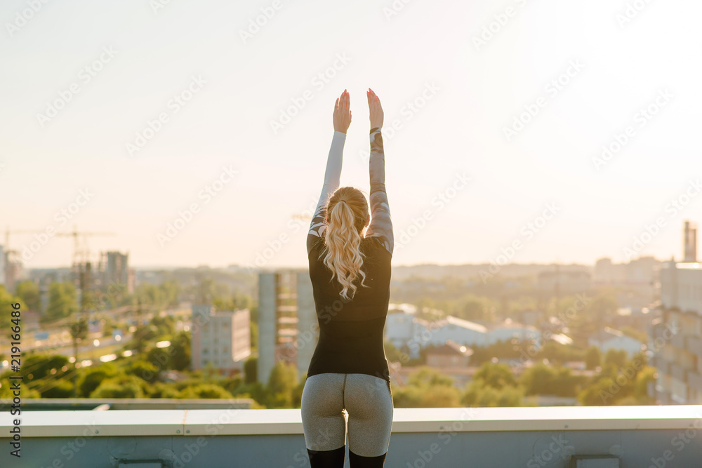 Fototapety, obrazy: Back view of beautiful sexy woman in stylish sportswear standing on the rooftop with beautiful city view on the sunset. After the workout. Hands up in the air
