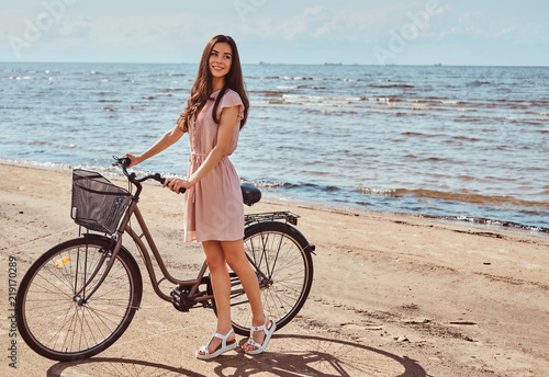 Fototapeta Smiling charming girl dressed in dress walks with her bicycle on the beach at a sunny day. obraz na płótnie