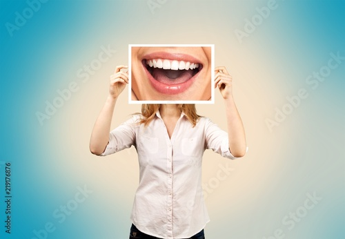 Woman holding picture with big smile. concept photo over dark