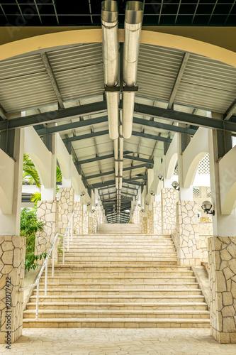 Fotografie, Tablou  Exterior multi level hallway/corridor with stone wall design in the Caribbean