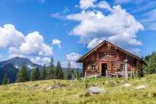 Almhütte In Den Bergen: Bäume, Grüne Wiese Und Blauer Himmel