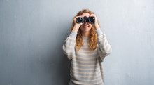 Young Redhead Woman Over Grey Grunge Wall Looking Through Binoculars With A Happy Face Standing And Smiling With A Confident Smile Showing Teeth
