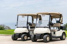 Two Empty White Golf Carts Par...