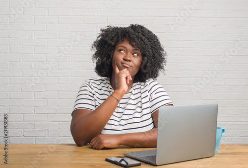 Foto Young african american woman sitting on the table using computer laptop serious