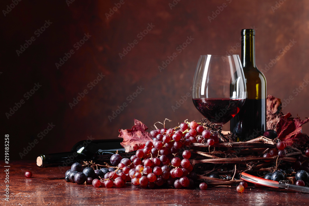 Red wine and fresh grapes with dried up vine leaves.