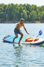 Child Boy Falling From A Paddleboard Into The Water