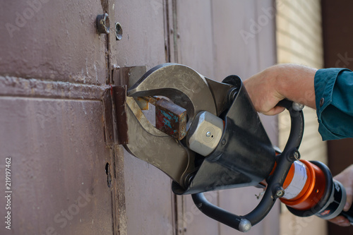 Fotografie, Obraz  Fire fighter with a hydraulic cutter in his hand cuts the door lock