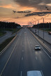 Highway traffic in sunset. minivan on the asphalt road with metal safety barrier or rail. Pine forest on the background