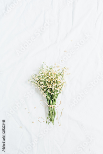 Lily of the valley flowers on white background. Flatlay, top view minimal floral concept.