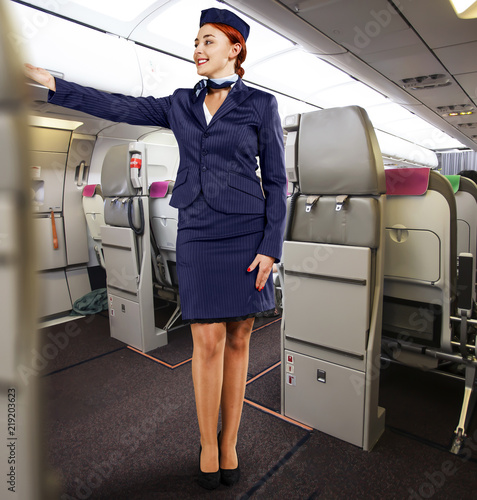 Carta da parati slim young stewardess woman and plane interior