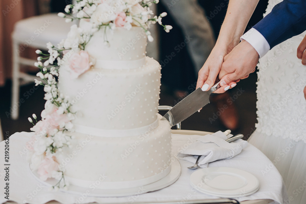 Fototapeta bride and groom holding knife and cutting stylish white wedding cake with flowers. modern big wedding cake with pink and white roses. luxury catering in restaurant. wedding reception