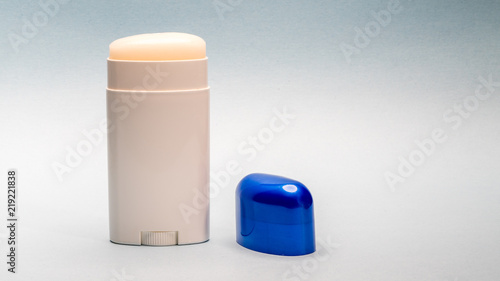 Photo Deodorant stick roll on, with blue cap next to it.