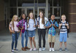 canvas print picture - Large Group portrait of pre-adolescent school kids smiling in front of the school building. Back to school photo of a diverse group of children wearing backpacks and ready to go to school