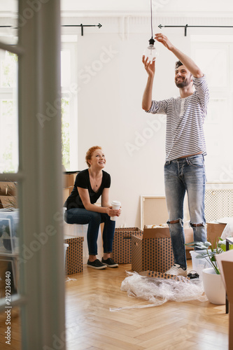 Smiling Man Hanging Lamp While Furnishing New Home After Moving In With His  Happy Wife