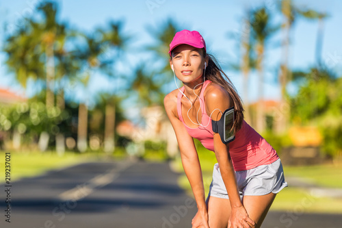 Tired runner woman ready for running wearing sports cap and sport armband  with earphones listening to mobile music. Active fit Asian girl resting  taking a ... f7ff4abd94e