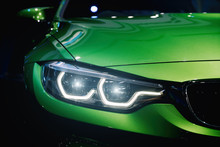 Closeup Headlights Of Modern Car During Turn On Light In Night.