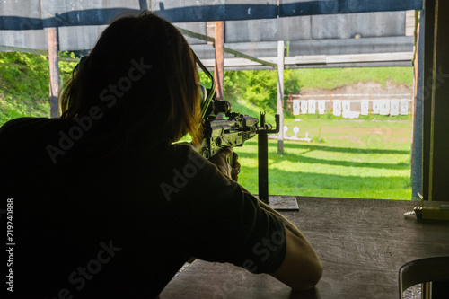 Girl shooting from rifle at shooting range - Buy this stock photo