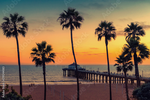 California beach at sunset, Palm trees and Pier on Manhattan Beach in California, Los Angeles. Vintage processed.