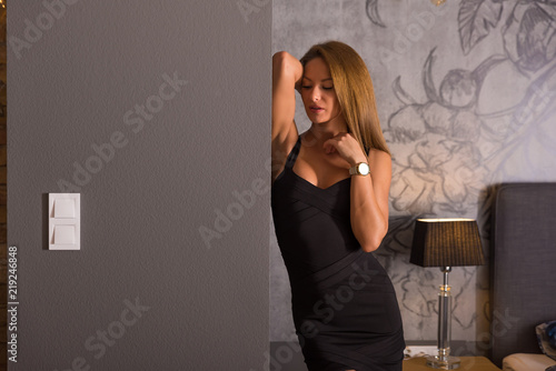 Fototapeta Sensual photo of a beautiful woman in an elegant black dress while standing against a wall in a modern apartments bedroom. obraz