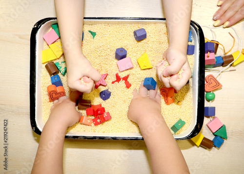 Valokuva  Children playing with kinetic sand, croup and designer in preschool