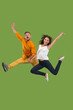 Freedom in moving. Pretty young couple jumping against green background