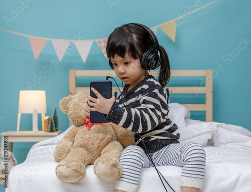 Fotografie, Obraz  Cute little girl singing with smartphone with teddy bear in her bedroom, Happy a