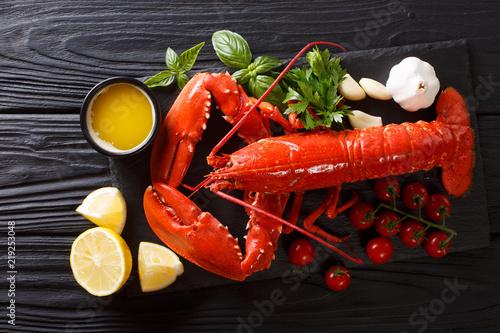 Drogie jedzenie organiczne: gotowany homar z cytryną, czosnkiem, świeżymi pomidorami i ziołami z bliska na stole. poziomy widok z góry