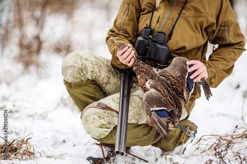 Female hunter in camouflage, armed with a rifle, standing in a snowy winter forest with duck prey
