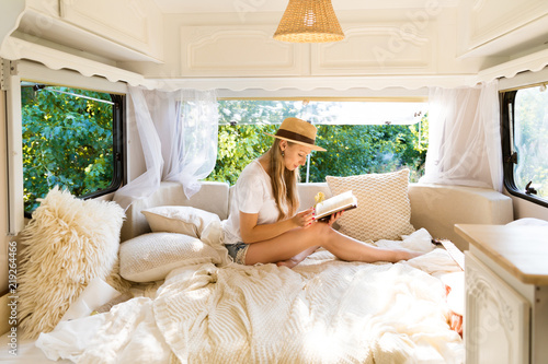 Fotografie, Obraz  Beautiful happy girl in bed in the morning by the window of a van with a book
