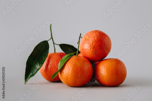 Unpeeled bright tangerines with leaves