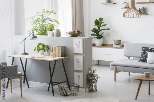 Fotografie, Obraz  Real photo of bright living room interior with half-wall with posters and desk w