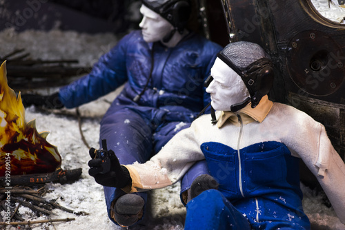 A astronaut and cosmonaut warming around the fire perform work on a strange cold planet