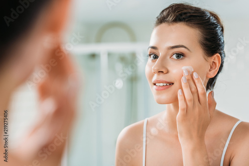 Fotografía  selective focus of smiling young woman applying face cream and looking at mirror