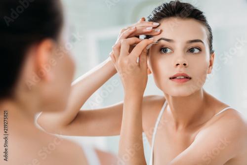 Obraz na płótnie beautiful girl correcting eyebrows with tweezers and looking at mirror in bathro