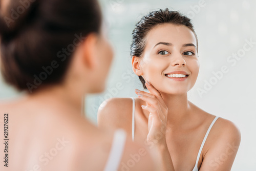 Fotografia beautiful smiling young woman touching skin and looking at mirror in bathroom