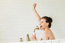 Beautiful Happy Girl Singing And Having Fun In Bathtub