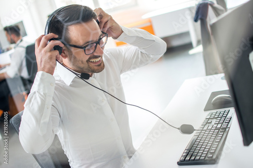 Smiling male customer technical support telephone worker using headphones with microphone and talking with client