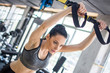 Young sporty woman doing push ups training arms with trx fitness straps in gym
