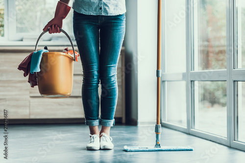 Fototapeta Young Woman holds Bucket with Cleaning Equipment