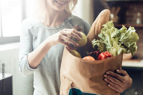 Closeup of Smiling Girl holds Bag of Healthy Food