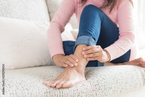 Photo Closeup woman sitting on sofa holds her ankle injury, feeling pain